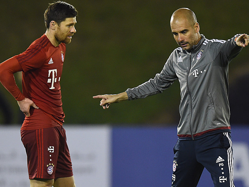 DOHA, QATAR - JANUARY 06: Head coach Josep Guardiola gives instructions to Xabi Alonso during a training session at day one of the Bayern Muenchen training camp at Aspire Academy on January 6, 2016 in Doha, Qatar. (Photo by Lars Baron/Bongarts/Getty Images)