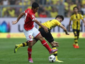 DORTMUND, GERMANY - AUGUST 27:  Yoshinori Muto of Mainz is challenged by  Julian Weigl of Dortmund during the Bundesliga match between Borussia Dortmund and 1. FSV Mainz 05 at Signal Iduna Park on August 27, 2016 in Dortmund, Germany.  (Photo by Lars Baron/Bongarts/Getty Images)
