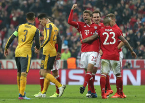 MUNICH, GERMANY - FEBRUARY 15:  Thomas Mueller of FC Bayern Muenchen celebrates his goal together with teammates Mats Hummels, Arturo Vidal and Joshua Kimmich (3rdL-R) as Kieran Gibbs (L) and Granit Xhaka (2ndL) of Arsenal FC react during the UEFA Champions League Round of 16 first leg match between FC Bayern Muenchen and Arsenal FC at Allianz Arena on February 15, 2017 in Munich, Germany.  (Photo by A. Beier/Getty Images for FC Bayern)
