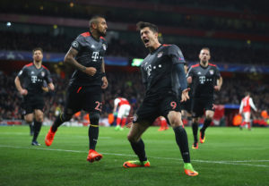 LONDON, ENGLAND - MARCH 07:  Robert Lewandowski of Bayern Muenchen (9) celebrates with team mates as he scores their first goal from a penalty during the UEFA Champions League Round of 16 second leg match between Arsenal FC and FC Bayern Muenchen at Emirates Stadium on March 7, 2017 in London, United Kingdom.  (Photo by Clive Mason/Getty Images)