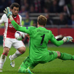 Schalke's goalkeeper Ralf Faehrmann (R) and Ajax Amsterdam's midfielder Amin Younes vie for the ball during the UEFA Europa League football match between Ajax Amsterdam and Schalke 04 on April 13, 2017 in Amsterdam, Netherlands. / AFP PHOTO / PATRIK STOLLARZ        (Photo credit should read PATRIK STOLLARZ/AFP/Getty Images)